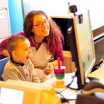 Un piccolo paziente durante un test audiologico con una studentessa volontaria